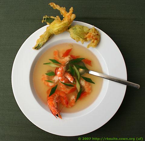 Kalte, leicht gelierte Tomatenconsommé mit Garnelen und gebackenen Zucchiniblüten